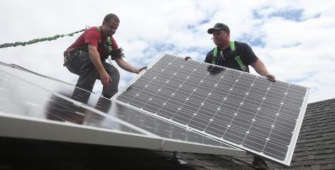 Dan Gutridge, left, and Randy Sunset install solar panels on a home in Southeast Portland in July.