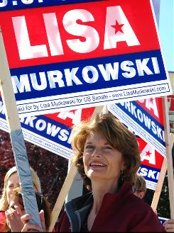 Sen. Lisa Murkowski, R-Alaska, joins volunteers to wave to motorists on Monday in Anchorage.
