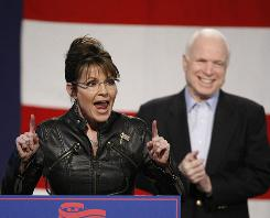 Sen. John McCain, background right, and Sarah Palin, former Alaska governor and Republican vice presidential nominee, make a campaign appearance at the Pima County Fairgrounds in Tucson in March.