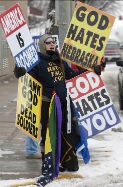 Shirley Phelps-Roper protests with signs that have offended some people in Bellevue, Neb., in December 2009.