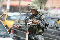 An Iraqi soldier hands out leaflets asking residents to keep watch for militant activity in Baghdad on Tuesday. The number of U.S. forces in Iraq has been drawn down to 50,000.