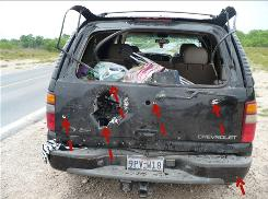 Bullet and blast holes cover the back of the Almanza family's car near Ciudad Mier, Mexico, on April 4. Almanza, who imports used cars, had bought the vehicle in Texas two weeks earlier.