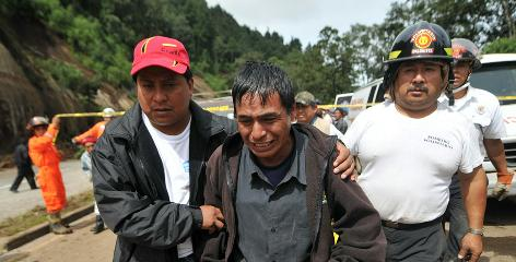 Manuel Ajtzalam is led from the scene after he identified the corpse of his nephew Manuel Sohon, buried by a landslide on Sunday west of Guatemala City.