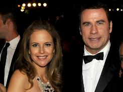 A judge dismissed charges against two people accused of trying to extort money from Jonh Travolta, here with wife Kelly Preston, after the prosecutor said the actor no longer wanted to pursue a case stemming from the death of his teenage son.