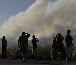 Spectators watch as the wildfire burns in Four Mile Canyon near Boulder, Colo., on Monday.