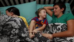 Lori Harrington rests with daughters Jasey, 12, left, and Kensley, 4, because the children have nightmares and anxiety at night four months after the Nashville flooding disaster.