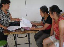 In Cloudy Ridge, China, census worker Wang Xiurong, left, asks Cao Xiurong, center, to check her household documents for the national tally.