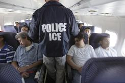 An ICE agent checks on shackled Mexican immigrants on a jet for deportation in May.