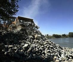Rocks are placed into position to shore up a levee along the Sacramento River near Knights Landing, Calif., on July 11, 2006.