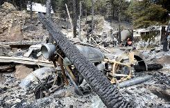 A motorcycle is among the ruins of a home consumed by a wildfire. The fire has destroyed 169 homes.