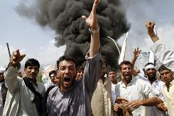 Afghans shout anti-U.S. slogans as they burn tires and block a highway during a protest in reaction to a small American church's plan to burn copies of the Quran, at Jalalabad, east of Kabul, Afghanistan, Friday.