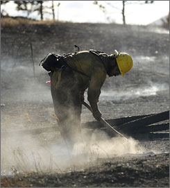 David Yowell, of El Paso County Wildland Fire Crew, works on putting out hot spots in Sunshine Canyon.