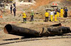 A portion of a natural gas line lies on a road Saturday in San Bruno, Calif., the scene of a huge explosion Thursday.
