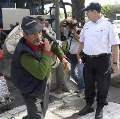 A police officer watches Roma, also known as Gypsies, arrive at Marseille airport, southern France, before being expelled from France on Tuesday.