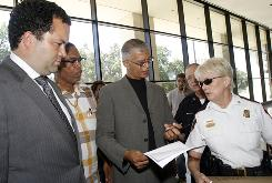 Benjamin Jealous, president of the NAACP, left, and forrmer Jackson attorney Chokwe Lumumba, second from right, present Capitol Police Maj. Johnnie Stewart a box filled with copies of petitions and letters of support for Jamie and Gladys Scott, sisters who have been jailed by the state for armed robbery,