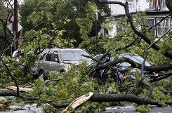 Cars are covered in debris after a severe storm moved through the area Thursday in the Queens borough of New York.