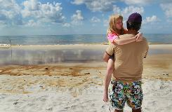 Pete Duchock looks out at the oil residue at Orange Beach, Ala., in June as he holds his daughter, Maddie. The oil washed ashore from the Deepwater Horizon spill in the Gulf.