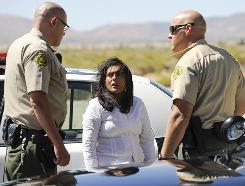 Los Angeles County Sheriff's officers speak to sect leader Reyna Marisol Chicas on Sunday after her group was located in Jackie Robinson Park in Littlerock, Calif.