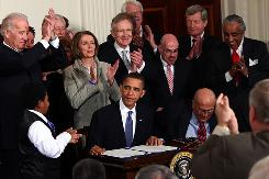 President Obama gets a round of applause from fellow Democrats after signing the Affordable Health Care for America Act at the White House on March 23.