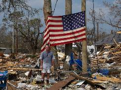 Bryan Pittari stands among the remains of his business in Long Beach Mississippi in September 2005. He and his wife found the flag while looking through their remains and hung the flag. Nearly $6 billion in surcharges were imposed after the 2005 hurricanes, including $4.2 billion in Florida and $500 million in Mississippi and Texas.