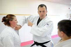 Exonerated: David Sipe, center, teaches a judo move to Alisha Burt and Jonny Losey in Burlington, Wash. As a Border Patrol agent, Sipe was acquitted of using excessive force after proving that prosecutors had withheld evidence about government favors to the illegal immigrants who testified against him.