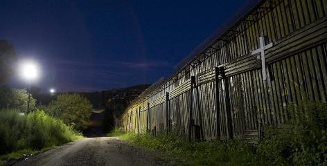 A floodlight illuminates a cross on the fence separating Nogales, Ariz., from Mexico.