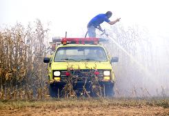 Bartholomew County volunteer firefighters work to put out a field fire near Columbus, Ind.