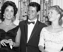 Elizabeth Taylor, Eddie Fisher and Debbie Reynolds, from left to right, are shown attending the opening show starring Fisher at the Tropicana, on June 19, 1958 in Las Vegas.