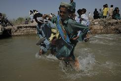 A Pakistani man who survived floods crosses a broken road in a flooded area in Sujawal, Sindh Province, southern Pakistan, Saturday.