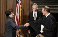 Elena Kagan shakes hands with Chief Justice John Roberts after becoming the Supreme Court's newest member on Aug. 7. Jeffrey Minear, counselor to the chief justice, held the Bible for the ceremony.
