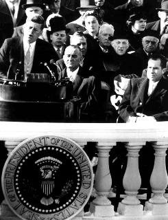 John F. Kennedy delivers his inaugural address in Washington in January of 1961 as incoming Vice President Lyndon B. Johnson and outgoing vice president Richard Nixon, right, look on.