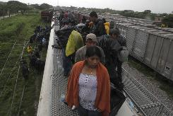 Central American migrants ride on top of a northern-bound train in Oaxaca, Mexico, on Aug. 31.