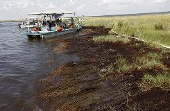 Workers on boats participating in the vessels of opportunity program try to clean shoreline impacted by the Deepwater Horizon oil spill in Bay Jimmy in Plaquemines Parish, La.