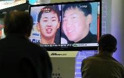 South Korean men watch a public TV screen showing what is believed to be the picture of Kim Jong Un, the youngest son of North Korean leader Kim Jong Il, at a railway station in Seoul on Tuesday.