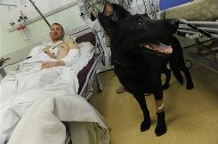 U.S. Air Force Staff Sgt. Brent Olson, 24, of Indiana, recuperates in Kandahar, Afghanistan. He was wounded in an explosion during operations that also injured his German shepherd military working dog Blek.
