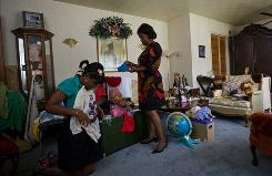 Monika Grundy, left, and her mother, Vel, fold clothes in their living room that doubles as Monika's walk-in closet.