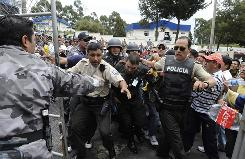 Ecuadorean riot policemen arrest a presidential bodyguard in front of the Police Hospital in Quito on Thursday.