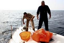 Italian Coast Guard officers inspect gear recovered off the southern Adriatic sea on Friday. The disappearance of two of the world's most acclaimed balloonists, Richard Abruzzo and Carol Rymer Davis, has created a somber mood for balloonists at the Albuquerque International Balloon Fiesta.