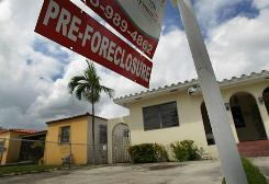 A pre-foreclosure sign is seen in front of a home in Miami on Sept. 16. The decision by Old Republic National Title Insurance to stop writing new polices for certain foreclosures could have major ramifications for the housing industry.