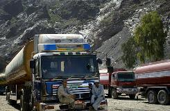 Pakistani drivers sit on a front bumper of a truck carrying supplies for NATO forces parked with other trucks at a roadside near the boarder crossing with Afghanistan in Torkhum, Pakistan, on Saturday.