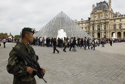 A French soldier patrols around the Louvre museum in Paris on Sunday. The State Department cautioned vigilance for Americans traveling in Europe.