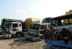 Pakistani drivers sit on a burnt out NATO oil tanker the morning after a Taliban attack hit a Afghanistan-bound supply convoy.