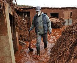 A Hungarian man walks through a yard that was flooded by toxic mud after a red sludge reservoir at a nearby alumina plant ruptured.