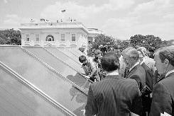President Jimmy Carter, center, is surrounded by reporters as he inspects a new White House solar hot water heating system on the roof of the West Wing in 1979.