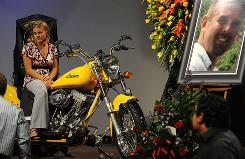 Tiffany Young Hartley sits on husband David's motorcycle after a service for him Tuesday in McAllen, Texas.