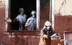 Firefighters clean a house flooded by toxic mud in Kolontar on Thursday.