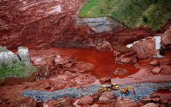 Excavators work at the broken dam of reservoir that contained red mud of an alumina factory near Ajka, Hungary.