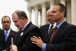Albert Snyder, center, is comforted by Kansas Attorney General Steve Six, right, before making a statement to reporters after the U.S. Supreme Court heard oral arguments Wednesday in the case Snyder v. Phelps, which tests the limits of the First Amendment.
