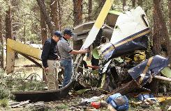 National Transportation Safety Board and Federal Aviation Administration workers survey the damage left by the crash of two medical helicopters in Flagstaff, Ariz., on June 30, 2008. All seven people on board the two aircraft were killed.