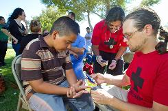 Edin Amaya, 12, gets checked Oct. 2 by Jason Odhner, right, at an event sponsored by Puente Arizona in Phoenix.
